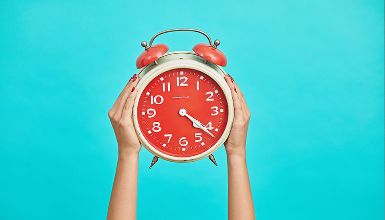 big red alarm clock on the blue background