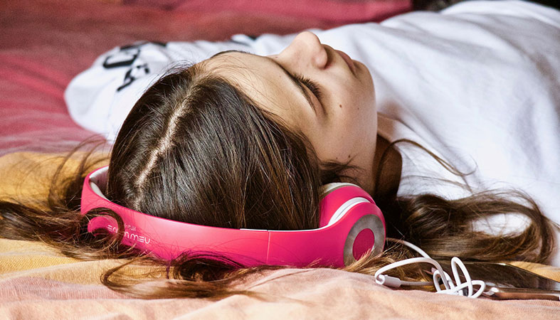 a girl is relaxing with the headphones on her head