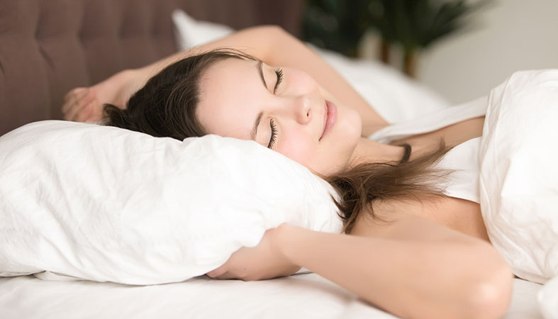 pretty young woman enjoys staying in bed a little more after sleep