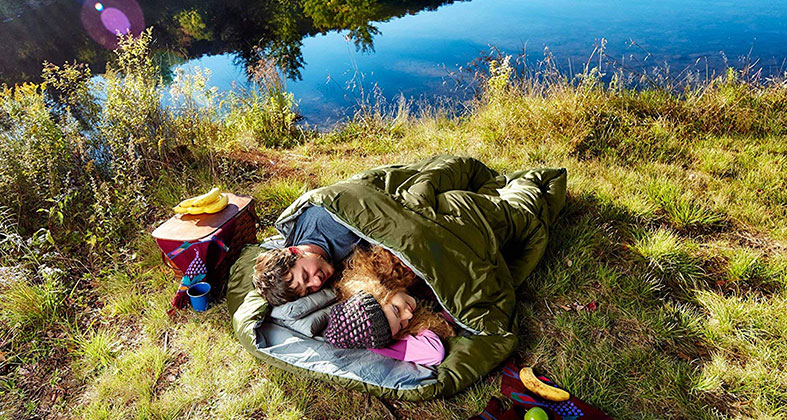 a couple is sleeping in the nature near lake in the sleeping bed