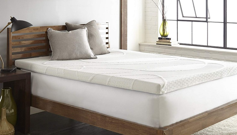 a bed with a mattress topper