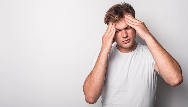 Close-up of young man suffering from headache