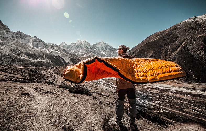 a man on the mountain is holding with his both hands a sleeping bag