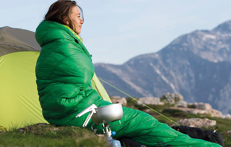 a woman is sitting outdoors in the green sleeping bag