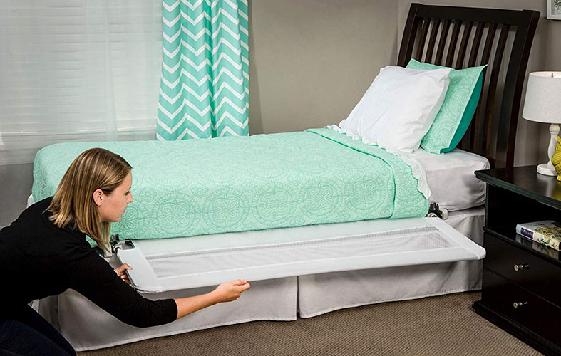 woman is putting a baby guard-for-the-bed