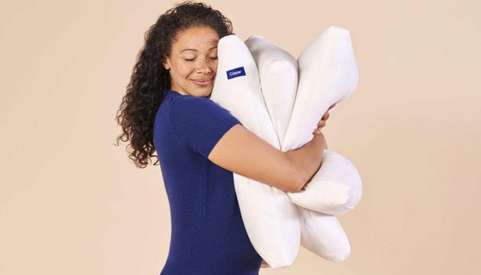 A woman is holding three Casper pillows