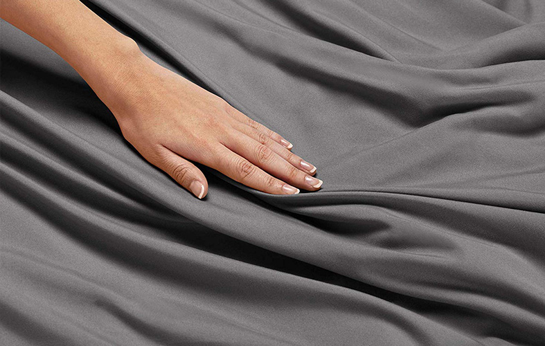 woman's hand is going through the silky sheet